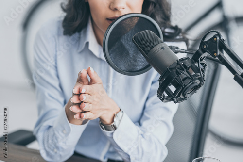 Photo cropped shot of radio host speaking in microphone in broadcasitng studio
