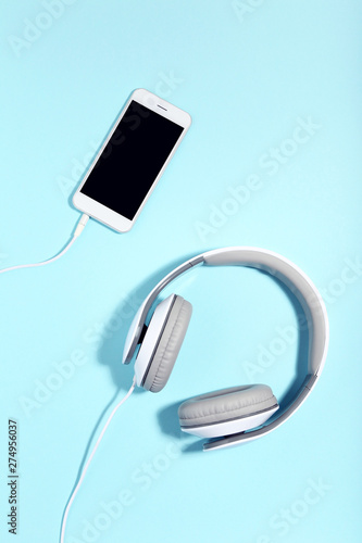 Headphones and smartphone on blue background. Minimalism concept