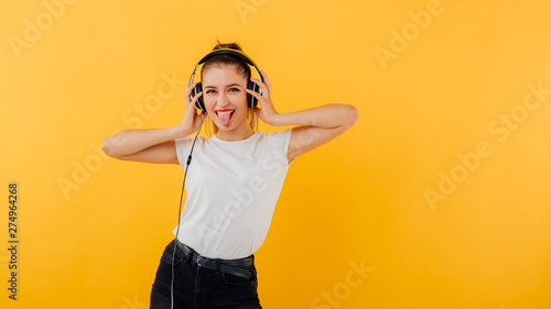 happy and distracted girl with headphones, dressed in a white shirt, positive emotional state isolated on a yellow background