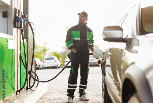 Gas station worker looking at pump