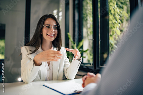 Photo Beautiful female financial adviser talking to a client.