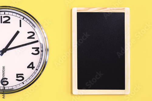 Obraz na plátně  Part of analogue plain wall clock and black notice board on trendy yellow background