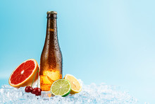Closed Bottle Of Brown Glass Beer On Ice. Fruits Lie Nearby. Concept Of Fruit Craft Beer Or Cider