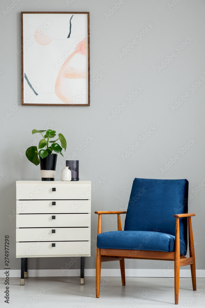 Fototapety, obrazy: Poster above white cabinet with plant next to blue wooden armchair in grey flat interior. Real photo