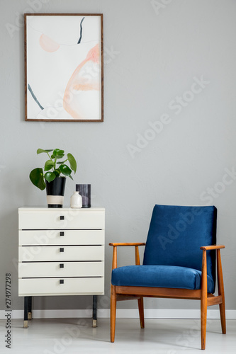 Poster above white cabinet with plant next to blue wooden armchair in grey flat interior. Real photo