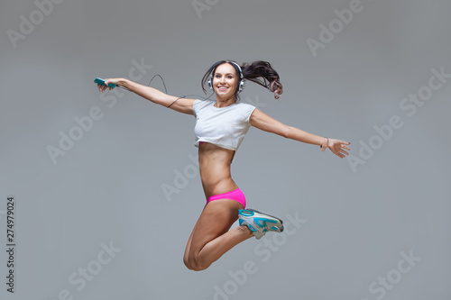 Energy young sexy brunette lady woman listening music in headphones isolated on gray background. Charming caucasian girl in earphones enjoying music and dancing. Jumping up, flying. - 274979024