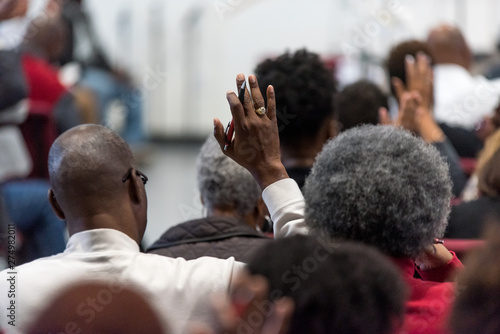Photo  African American Man in a White Suit at Church with His Hand Raised