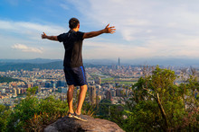 An Asian Tourist Man Hiking And Enjoying View On Rock, Mountain Hill In Taipei Downtown, Taiwan In Adventure Concept During Travel Trip, Vacation, Or Holidays. Skyscraper And High-rise Buildings View.