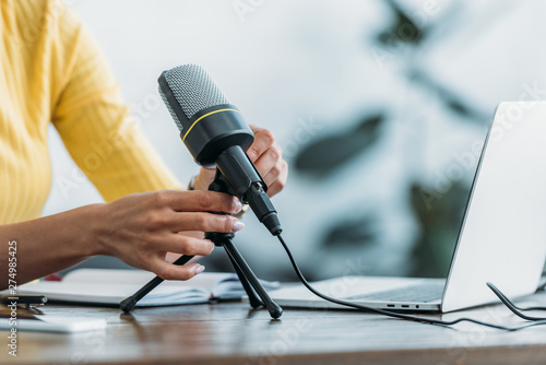 cropped view of radio host adjusting microphone while sitting at workplace in st Poster Mural XXL