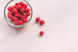 Leinwanddruck Bild - High angle view of red raspberries in glass bowl and scattered on pink striped background