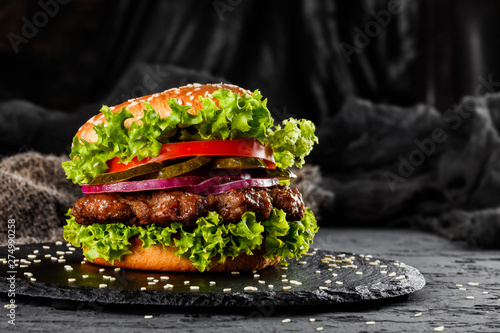 Fotografia, Obraz  Beef burger with tomatoes, red onions, cucumber and lettuce on black slate over dark background