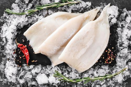 Slika na platnu Fresh raw fillet squid with spices and ice on slate stone on dark stone background