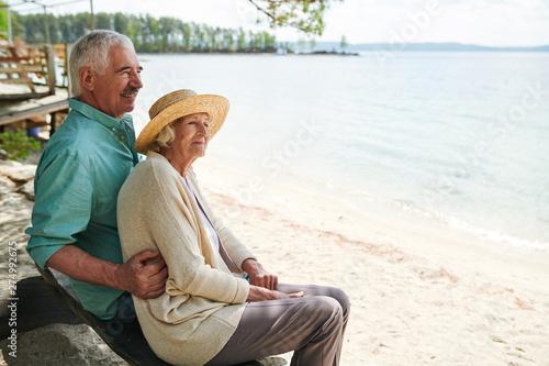 Senior romantic man and woman sitting on the beach
