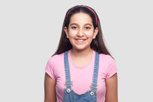 Portrait Of Happy Beautiful Brunette Young Girl In Casual Style, Pink T-shirt And Blue Denim Overalls Standing And Looking At Camera With Toothy Smile. Indoor Studio Shot, Isolated On Gray Background.