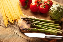 Asparagus, And An Artichoke A Sprig Of Tomatoes And Sweet Red Pepper And Italian Spaghetti On A Cutting Board With A Knife, Sliced. Tasty And Healthy Food, Restaurant Menu, Home Menu
