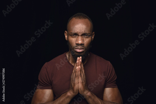 Close up portrait of young man isolated on black studio background Wallpaper Mural