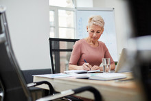 Portrait Of Mature Female Boss Working In Office Sitting At Table In Conference Room, Copy Space