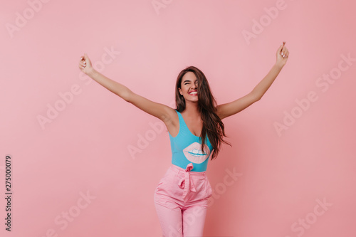 Foto auf Leinwand Tanzschule Blissful girl with tanned skin dancing with sincere smile on bright background. Wonderful brown-haired caucasian female model expressing happiness.