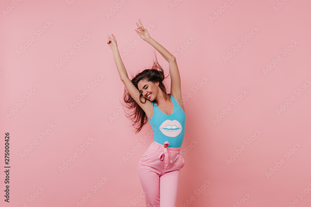 Fototapeta Lovely slim girl posing with sincere smile. Pretty long-haired female model dancing with hands up on pink background.