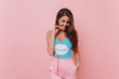 Tanned spectacular girl in funny tank-top posing on pink background. Indoor photo of brunette wonderful lady expressing positive emotions.