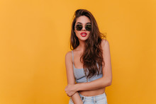 Lovely Dark-haired Woman In Trendy Sunglasses Playfully Posing In Studio. Wonderful European Girl With Tanned Skin Relaxing During Photoshoot.