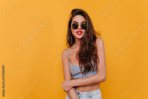 Foto auf Leinwand Friseur Lovely dark-haired woman in trendy sunglasses playfully posing in studio. Wonderful european girl with tanned skin relaxing during photoshoot.