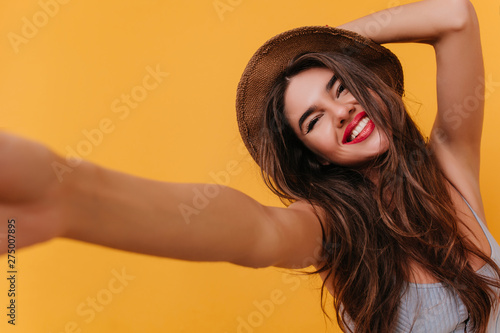 Fotomural Tanned lady with blissful face expression making selfie and laughing
