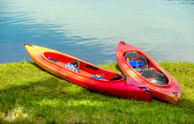 Red Canoe Lying In The Grass On The Lake