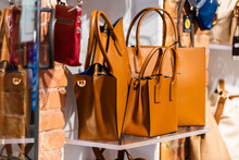 Many Leather Purse Bags In Siena Italy With Orange Brown Color Hanging On Display In Shopping Street Market In City