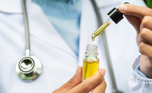 CBD Hemp Oil, Doctor Holding A Bottle Of Hemp Oil, Medical Marijuana Products Including Cannabis Leaf, Cbd And Hash Oil, Alternative Medicine