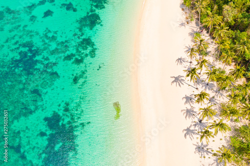 Fototapeta Turquoise lagoon with a coral reef and white beach. Beach with white sand and palm trees, view from above. Puka Shell Beach, Boracay Island, Philippines, aerial view. obraz na płótnie