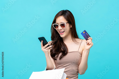 Fotografering  Charming young Asian lady happily holding credit card and phone