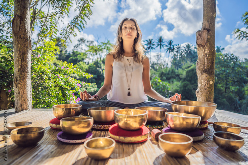 Woman playing on Tibetan singing bowl while sitting on yoga mat against a waterfall. Vintage tonned. Beautiful girl with mala beads meditating - 275034057