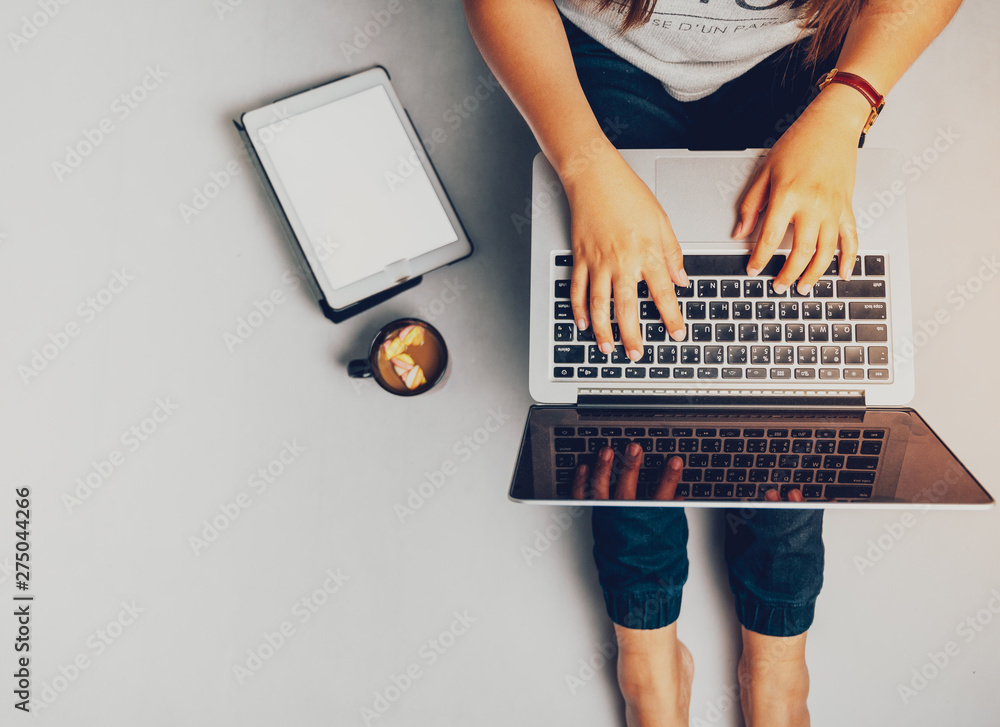 Fototapety, obrazy: Young woman working on laptop computer while sitting on the floor and holding hot coffee, vintage tone.