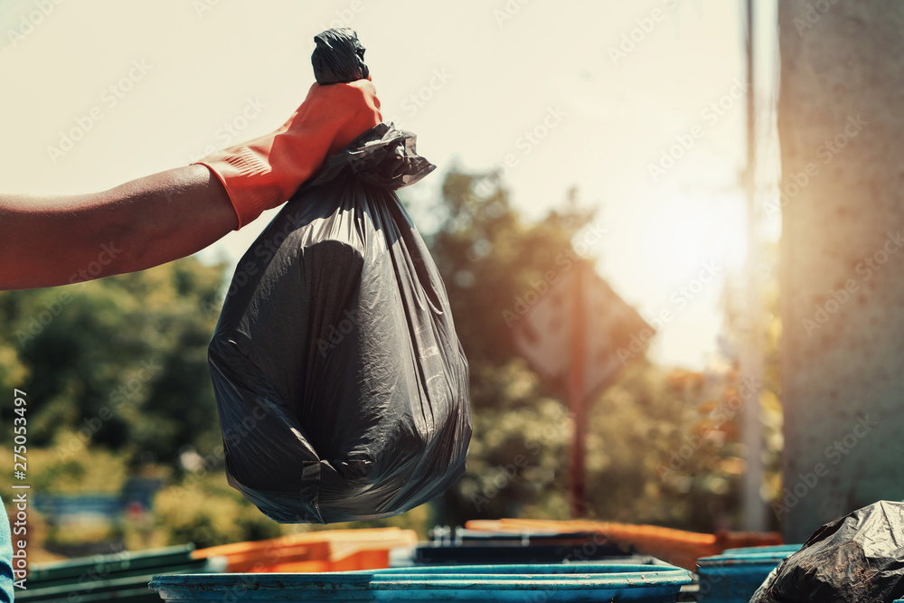 Fototapety, obrazy: hand holding garbage black bag putting in to trash