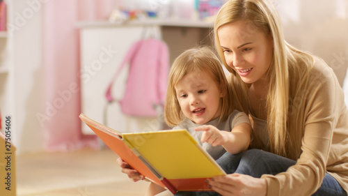 Beautiful Young Mother and Her Cute Little Daughter Read Children's Book Together Fototapet