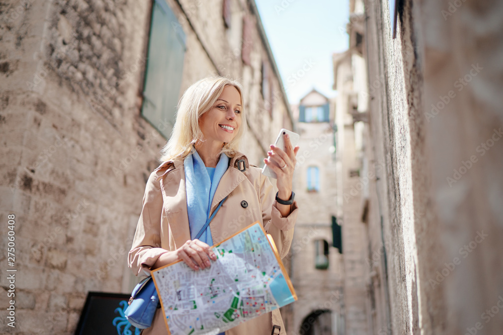 Fototapety, obrazy: App for tourism. Travel and technology. Pretty young woman with map using smartphone at old town. Travel by Europe.