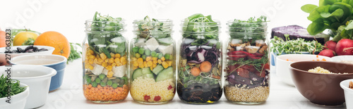 Pinturas sobre lienzo  tasty vegetable salad in glass jars on wooden white table isolated on white, pan