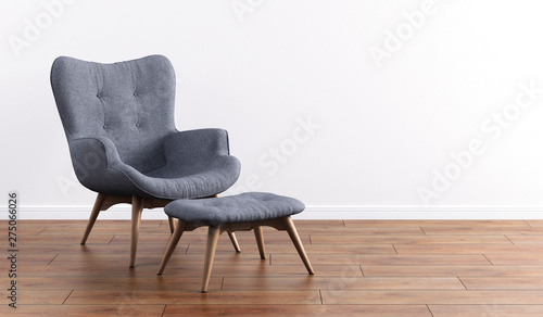 Fototapeta Fashionable modern gray armchair with wooden legs, ottoman against a white wall in the interior