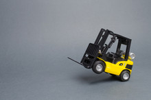 Yellow Forklift Truck Rides On The Rear Wheels On Gray Background. Warehouse Equipment, Vehicle. Logistics And Transport Infrastructure, Industry And Agriculture. Unloading, Transportation, Sorting
