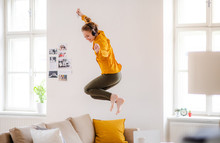 A Young Female Student With Headphones Jumping On Sofa When Studying.