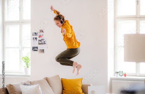 Fotografia A young female student with headphones jumping on sofa when studying