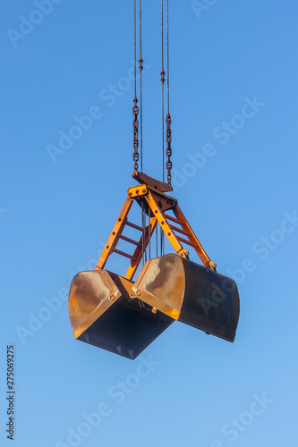 Tablou Canvas Closeup of the old rusty clamshell bucket suspended by wire ropes and chains aga
