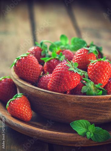 Fresh sweet strawberries on wooden bowl