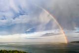 Fototapeta Tęcza - Stunning big rainbow after the rain over the sea