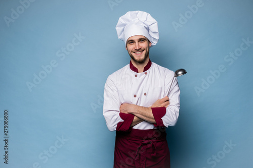 Fototapeta Portrait of positive toothy chef cook in beret, white outfit having tools in crossed arms looking at camera. obraz