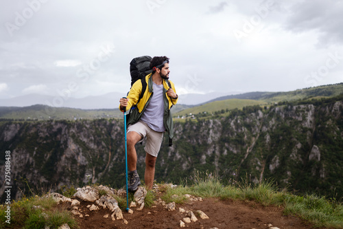 Fotografía  Young man traveling with backpack hiking in mountains