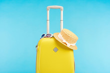 Yellow Colorful Travel Bag With Straw Hat And Sunglasses Isolated On Blue