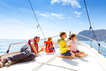 Two Little Kid Boys, Father And Toddler Girl Enjoying Sailing Boat Trip. Family Vacations On Ocean Or Sea On Sunny Day. Children Smiling. Brothers And Sister, Siblings And Dad Having Fun On Yacht.