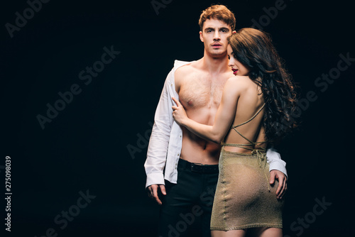 Obraz sexy brunette woman undressing boyfriend with muscular torso isolated on black with copy space - fototapety do salonu